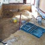 Oil contaminated soil being removed from inside a home